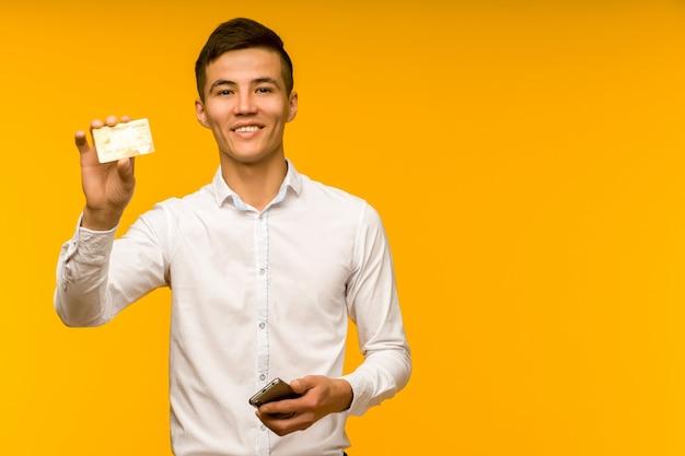 Ritratto di giovane uomo asiatico felice che tiene la carta di credito e che parla sul telefono