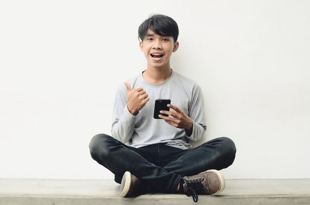 Un ritratto di giovane uomo asiatico felice che tiene un handphone