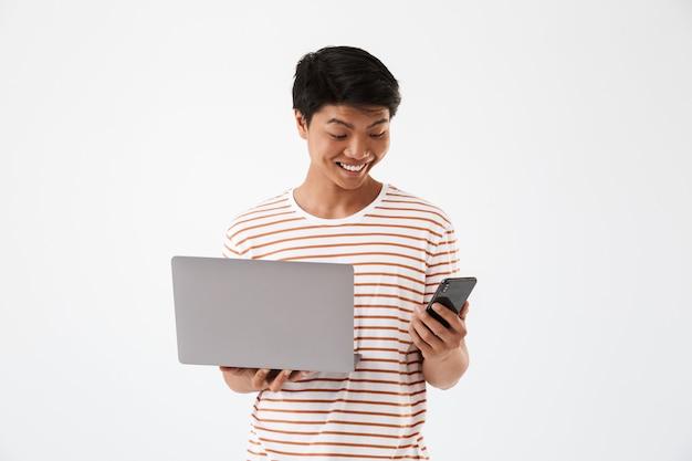 Ritratto di un felice giovane uomo asiatico tenendo il computer portatile
