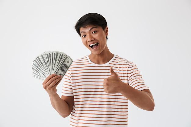 Ritratto di un giovane uomo asiatico felice che tiene i soldi