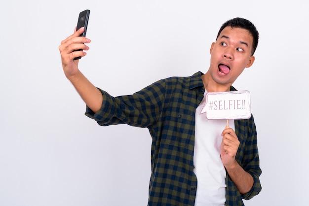 Ritratto di felice giovane uomo asiatico prendendo selfie con segno di carta