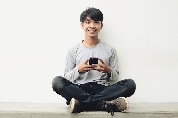 Ritratto di un giovane uomo asiatico felice che utilizza il telefono cellulare