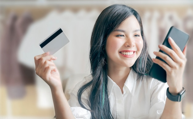 Ritratto di giovane donna asiatica felice che mostra la carta di credito e che per mezzo dello smartphone mentre comperando al centro commerciale.