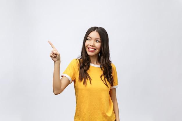 Ritratto di giovane donna asiatica felice con il dito rivolto verso l'alto