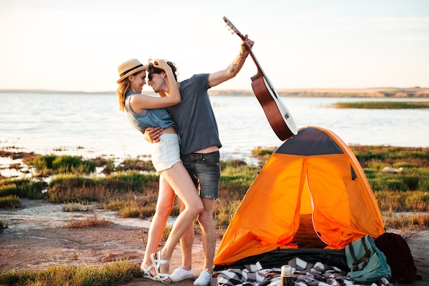 Ritratto di giovani coppie attraenti felici che abbracciano davanti alla tenda da campeggio