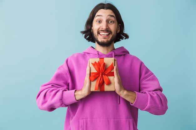 Ritratto di un giovane uomo bruna barbuto felice che indossa una felpa con cappuccio in piedi isolato sul muro blu, che mostra la scatola presente