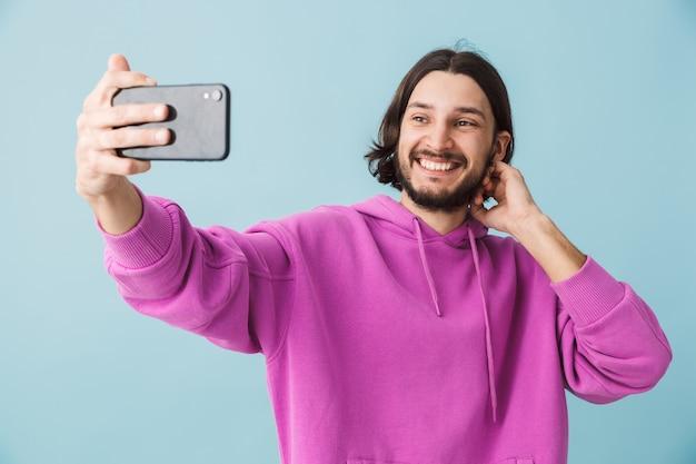 Ritratto di un giovane uomo bruna barbuto felice che indossa una felpa con cappuccio in piedi isolato sul muro blu, facendo un selfie