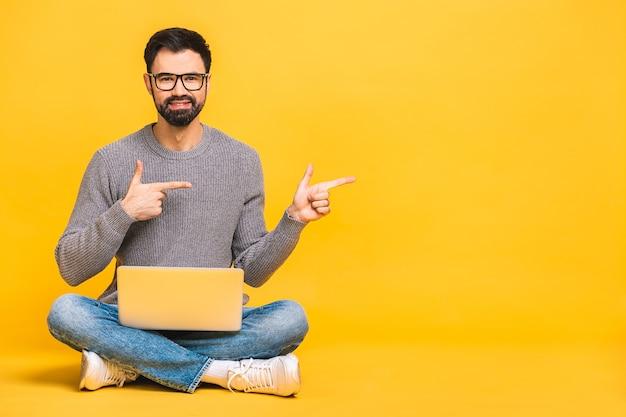 Ritratto di un giovane uomo barbuto felice in computer portatile azienda casual mentre è seduto su un pavimento isolato su sfondo giallo. dito puntato.