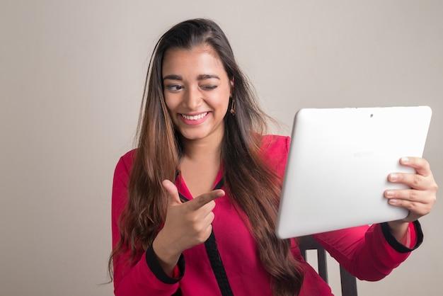 Ritratto di felice giovane bella imprenditrice indiana vlogging utilizzando la tavoletta digitale