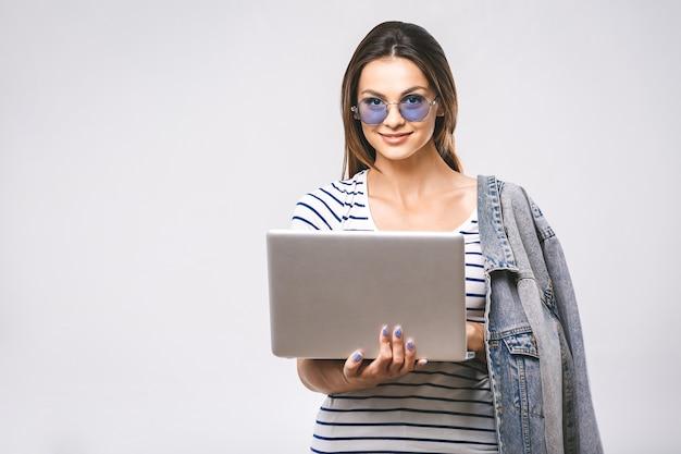 Ritratto di felice giovane bella donna sorridente in piedi con il computer portatile