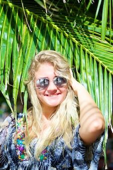 Ritratto di giovane bella donna felice in occhiali da sole con la palma tropicale sulla spiaggia al giorno di estate