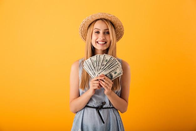 Ritratto di una giovane donna bionda felice in cappello estivo