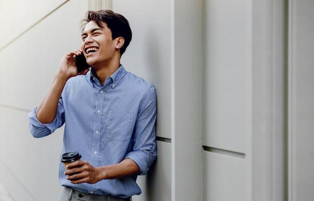 Ritratto di un giovane imprenditore felice utilizzando il telefono cellulare. stile di vita delle persone moderne. in piedi vicino al muro con una tazza di caffè