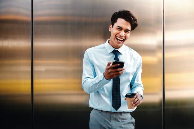 Ritratto di giovane uomo d'affari felice facendo uso del telefono cellulare nella città urbana.
