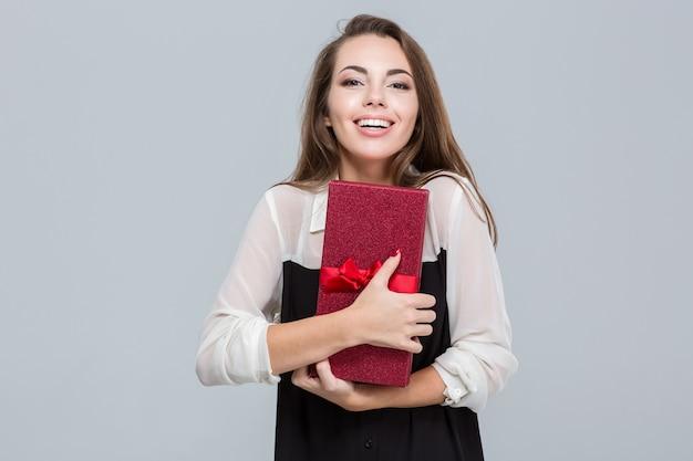 Ritratto di una giovane donna d'affari felice che tiene in mano una confezione regalo su sfondo grigio