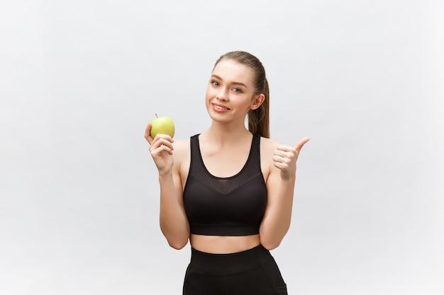 Ritratto di una giovane donna caucasica felice che tiene e che mangia mela verde
