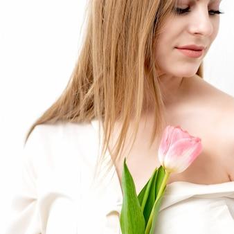 Un ritratto di una giovane donna caucasica felice con gli occhi chiusi e un tulipano rosa contro un muro bianco con spazio di copia