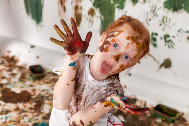 Ritratto di bambino felice che gioca con l'acquerello. viso di bambino e vestiti disordinati dipinti con vernici. concetto di divertimento per bambini, giochi d'arte e teppismo. immagine a colori per il festival di holi. copia spazio