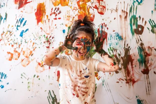 Ritratto di bambino felice che gioca con l'acquerello. volto di bambino e vestiti dipinti a caso con vernici. concetto di divertimento per bambini, giochi d'arte e teppismo. immagine a colori per il festival di holi. copia spazio