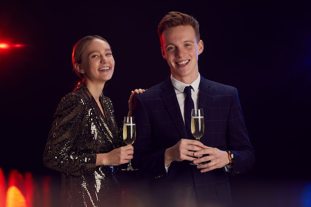 Ritratto di felice coppia giovane azienda bicchiere di champagne e guardando la fotocamera mentre posa alla festa in piedi su sfondo nero, copia dello spazio
