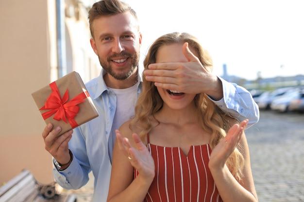 Ritratto di una giovane coppia felice che si abbraccia mentre sta in piedi insieme a una scatola regalo, l'uomo copre gli occhi della donna.