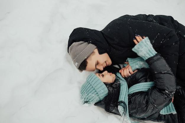 Ritratto di felice coppia giovane sdraiato sulla neve e guardando l'un l'altro.