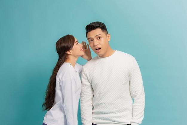 Ritratto di una giovane coppia felice in piedi insieme sul blu, raccontando i segreti