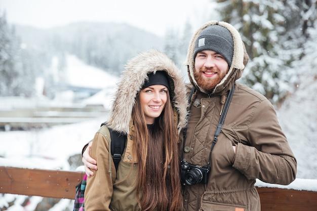Ritratto di giovane coppia felice con la macchina fotografica sulla località di soggiorno di montagna invernale