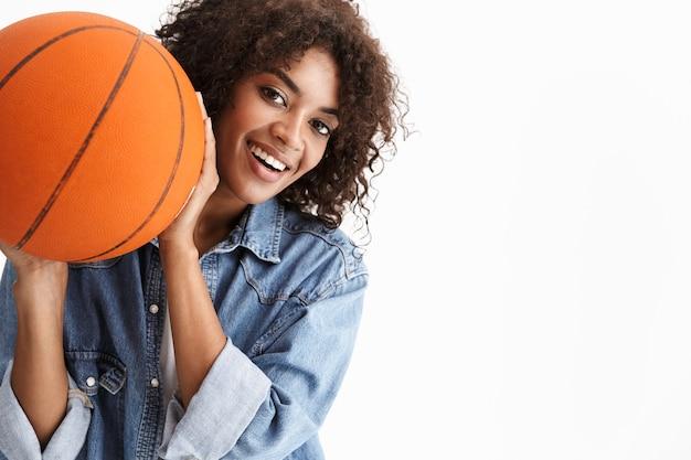 Ritratto di felice giovane donna sportiva eccitata africana in possesso di pallacanestro in posa isolata su muro bianco