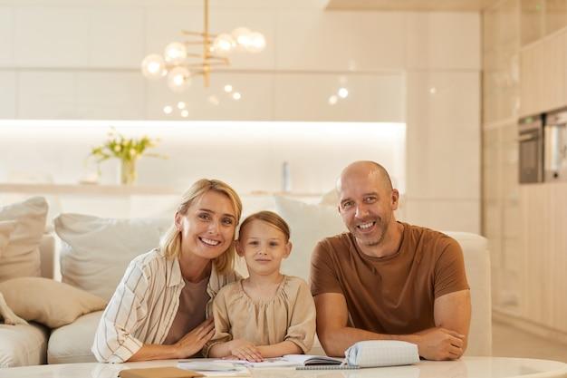 Ritratto di giovane famiglia felice che sorride mentre aiuta la bambina sveglia che attinge a studiare a casa