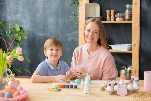 Ritratto di giovane famiglia felice seduto al tavolo di legno con barattoli di vernice e preparazione per la pasqua