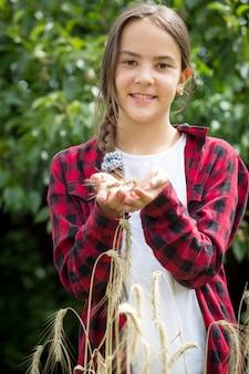 Ritratto di giovane agricoltore femminile felice che posa nel campo di grano al giorno soleggiato