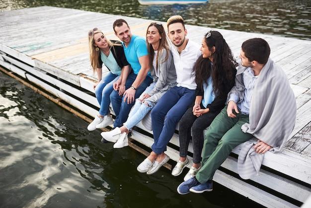 Ritratto di giovani amici felici seduti su un molo sul lago.