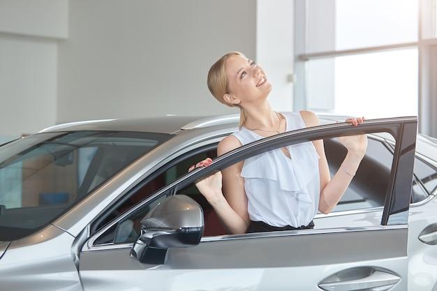 Ritratto di una giovane ragazza felice che acquista una nuova auto in una concessionaria
