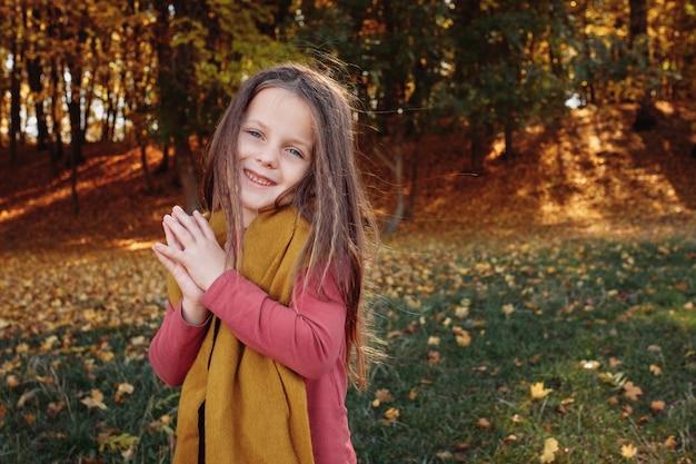 Ritratto di giovane ragazza felice che gode della giornata di sole nella foresta di autunno