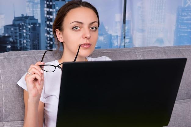 Ritratto di una giovane ragazza felice si mette gli occhiali alla bocca mentre lavora su un laptop facendo i suoi affari da casa seduta su un divano e sorridendo nel soggiorno in un'atmosfera rilassata