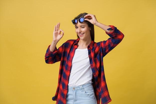 Ritratto di una giovane ragazza felice in abiti estivi che mostra gesto ok su sfondo giallo.