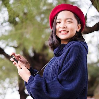 La ragazza felice del ritratto usa il maglione di usura del telefono cellulare e il cappello rosso sul fondo della natura Foto Premium
