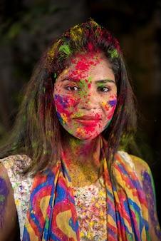 Ritratto di una giovane ragazza felice con un viso colorato in occasione del festival dei colori holi.