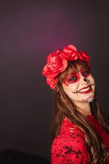 Ritratto di una giovane ragazza felice con il trucco di dia de los muertos con spazio di copia.