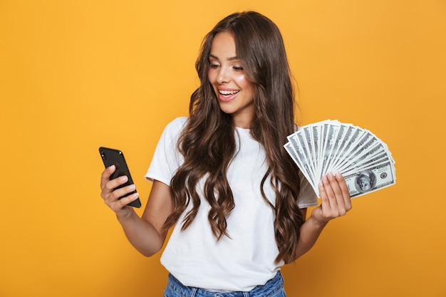 Ritratto di una giovane ragazza felice con lunghi capelli castani in piedi sopra il muro giallo, tenendo le banconote in denaro, utilizzando il telefono cellulare