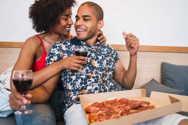 Ritratto di felice giovane coppia latina cenando insieme e bevendo vino a casa loro. stile di vita e concetto di relazione.