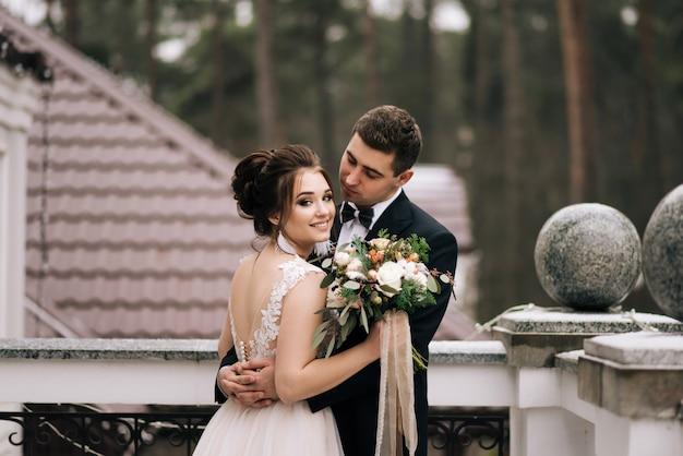 Ritratto di giovani amanti felici della sposa e dello sposo sul balcone di un bellissimo hotel. giorno del matrimonio