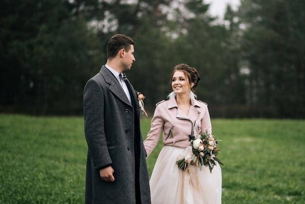 Ritratto di giovani sposi amorevoli felici. gli sposi corrono attraverso il campo con la prima neve. giorno del matrimonio