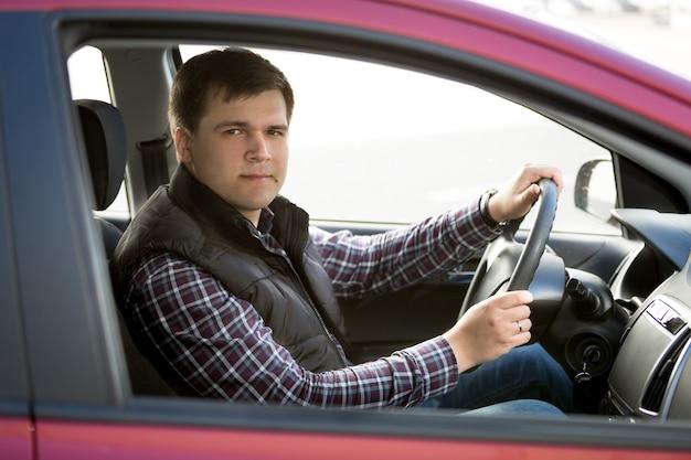 Ritratto di giovane uomo felice alla guida di una piccola auto