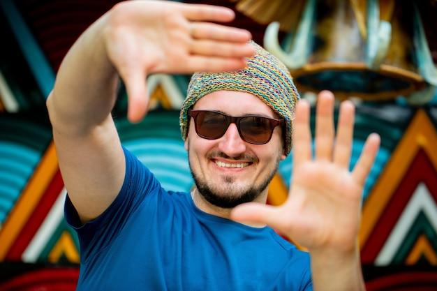 Ritratto di un giovane felice in un cappello e occhiali da sole sorridente per strada in una giornata estiva contro un muro luminoso