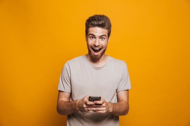 Ritratto di un giovane uomo felice che tiene il telefono cellulare