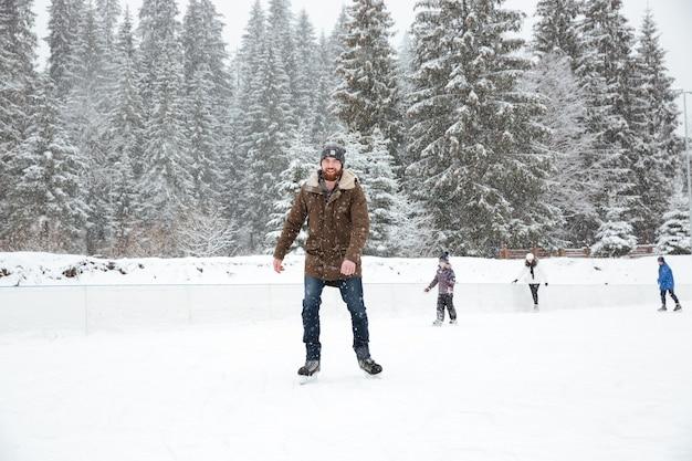 Ritratto di un giovane felice che pattina sul ghiaccio all'aperto