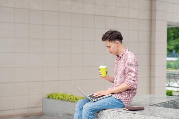 Ritratto di un giovane felice seduto sulle scale della città con un laptop