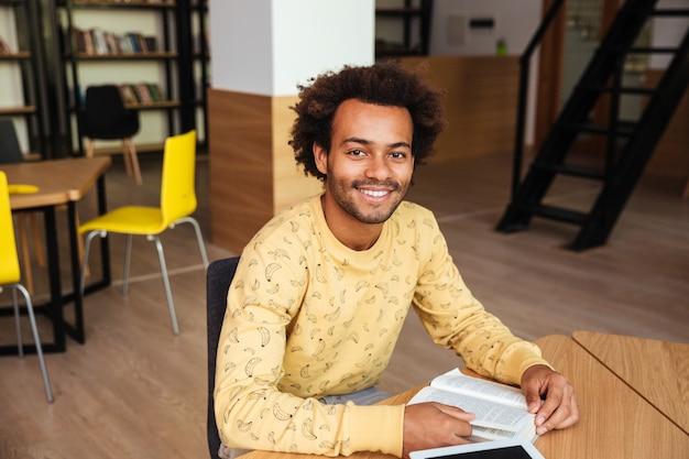 Ritratto di felice giovane uomo seduto e studiando in biblioteca